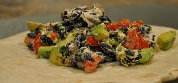 Stuffing ingredients in soft flour tortillas for Black Bean Burritos