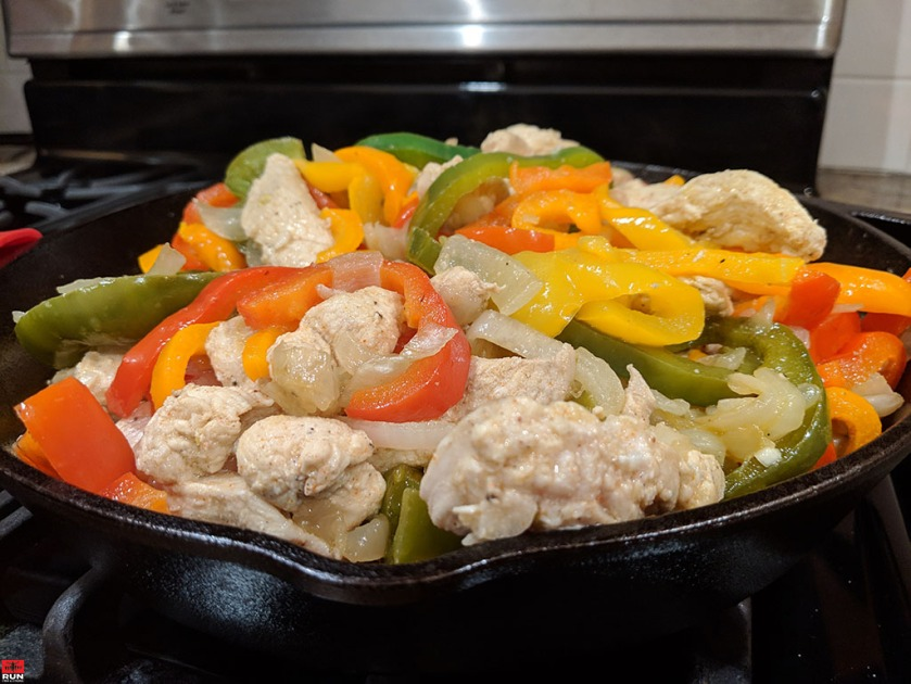 Add sauteed peppers and onions to cooked chicken for Chicken Fajitas