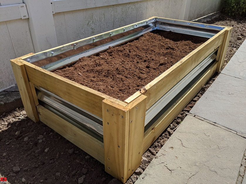 Garden Transformation filling raised bed with organic soil and peat moss